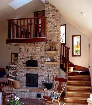 Centrally Located Masonry Heater Is The Focal Point Of The Living Room.  Heater Veneer Supports The Upper Landing.
